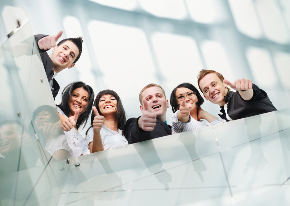 Happy employees looking down a stairwell giving a thumbs up.
