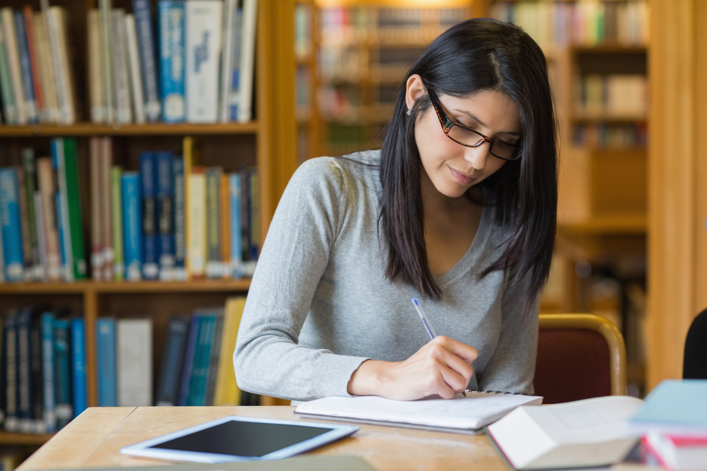 woman writing paper with research sources