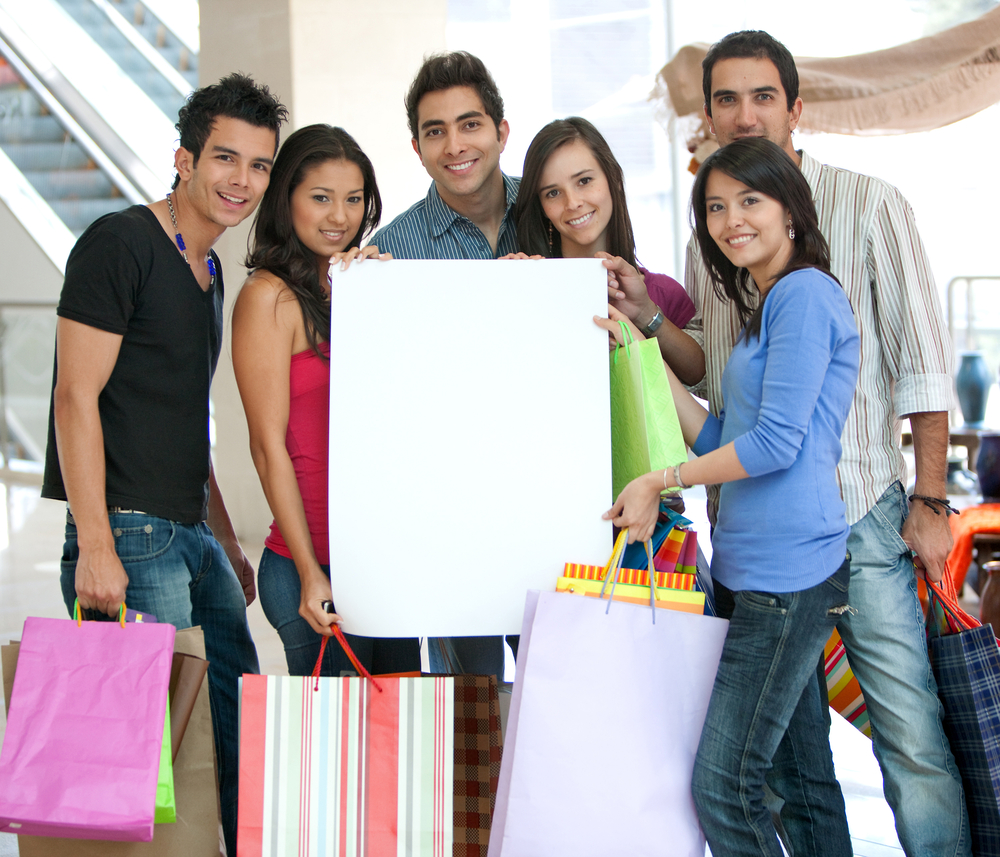 Group of shoppers holding a banner ad and some bags in a shopping mall