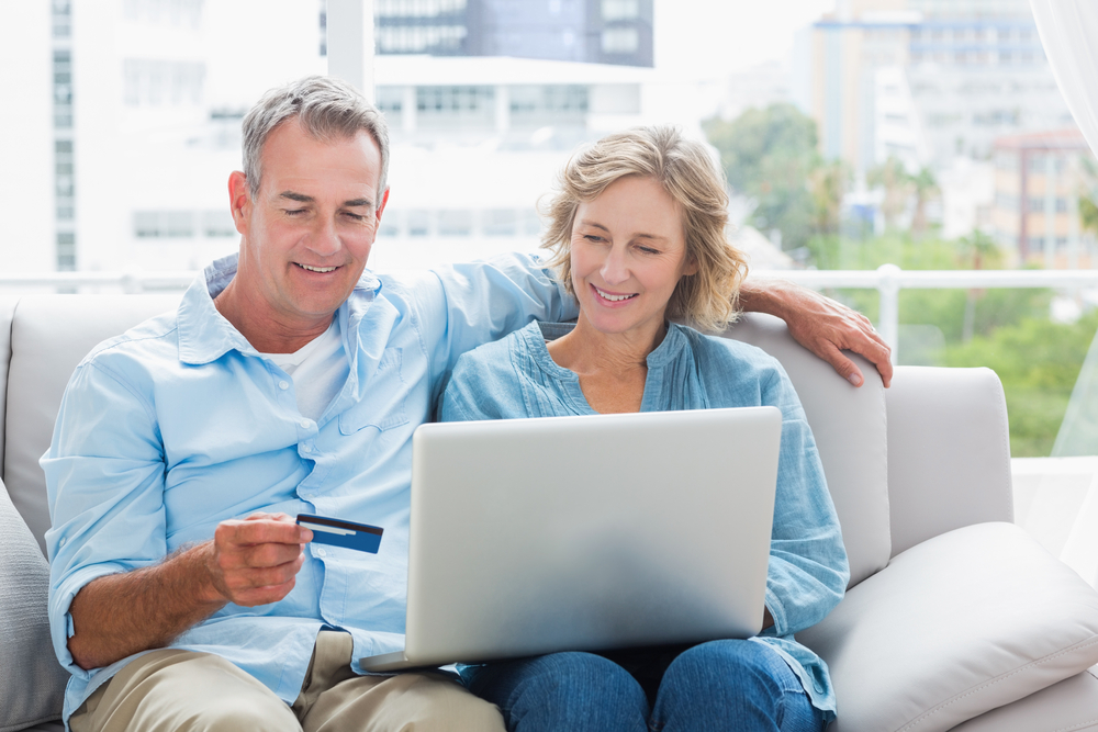 couple sitting looking at their computer and smiling