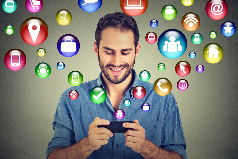 man on smartphone with social media icons flying around his head